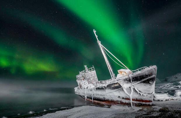 Мурманский фотограф Виталий Новиков изобразил под северным сиянием корабль, который в январе этого года штормом выбросило на берег села Териберка. Через пару недель после снимка корабль убрали