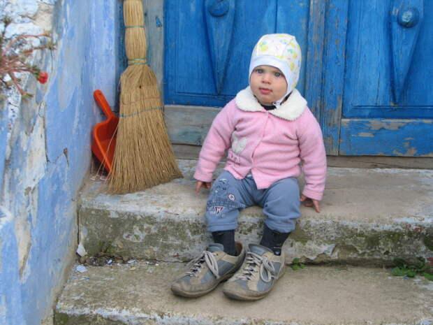 ребёнок сидит на ступеньках