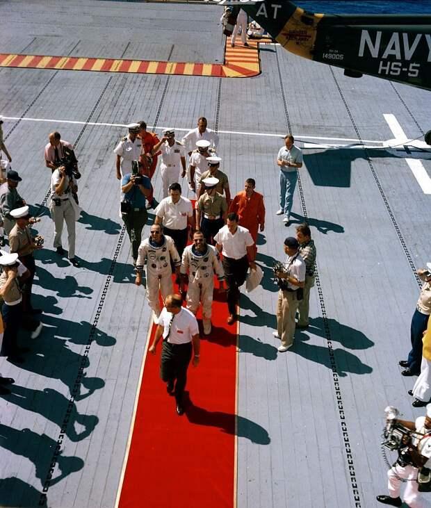 1965, 29 августа. Астронавты Л. Гордон Купер и Чарльз Конрад идут по красному ковру на борту авианосца USS Lake Champlain после приводнения