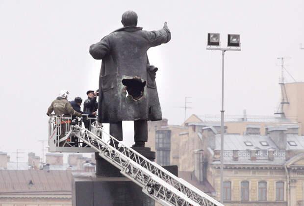Эксперты-криминалисты изучают отверстие от взрыва бомбы, заложенной в памятник Владимиру Ленину в Санкт-Петербурге