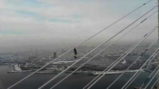 Альпинист на 300-метровой высоте снял клип о своей работе по очистке Русского моста ото льда (1 фото + 1 видео)