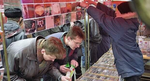 Молодые люди выбирают музыкальные диски сомнительного лицензирования. Один из них, с плохим зрением, аккуратно придерживает початую бутылку пива и готовится отведать жменю семян, конец 90-х Горбушка
