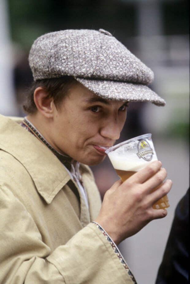 """Посетитель фестиваля пива в парке """"Эрмитаж"""" пугливо пригубливает пиво из пластикового стаканчика, 1998 год"""