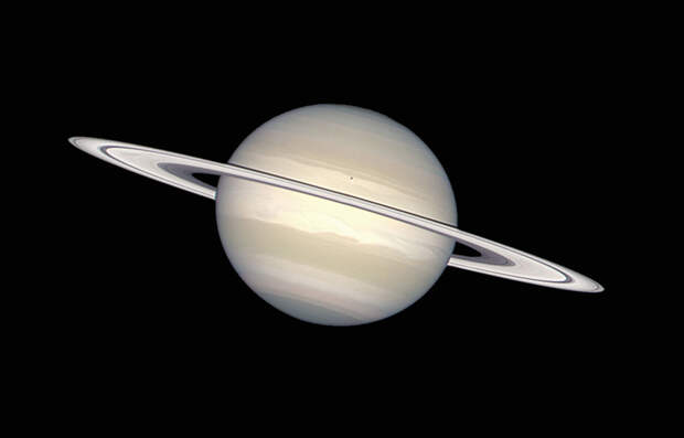 The ring swirling around Saturn consists of chunks of ice and dust. Saturn itself is made of ammonia ice and methane gas. The little dark spot on Saturn is the shadow from Saturn's moon Enceladus.