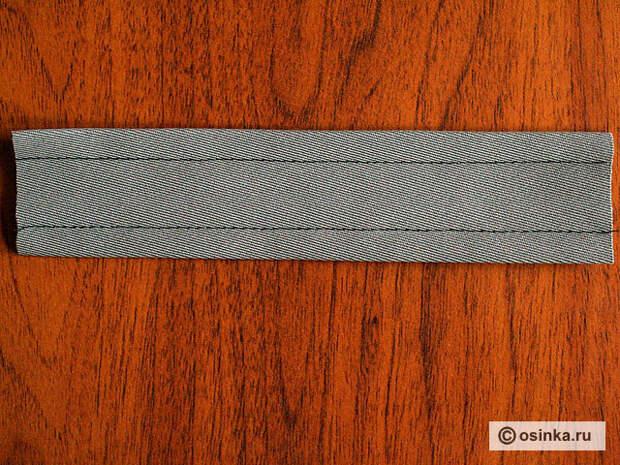 07. Проложите сдерживающие строчки на расстоянии 1/2 высоты рамки от сгибов или выставьте на лапке с навесным кронштейном необходимое расстояние. Следите, чтобы с изнанки оверложенный край обтачки не попал под строчку.