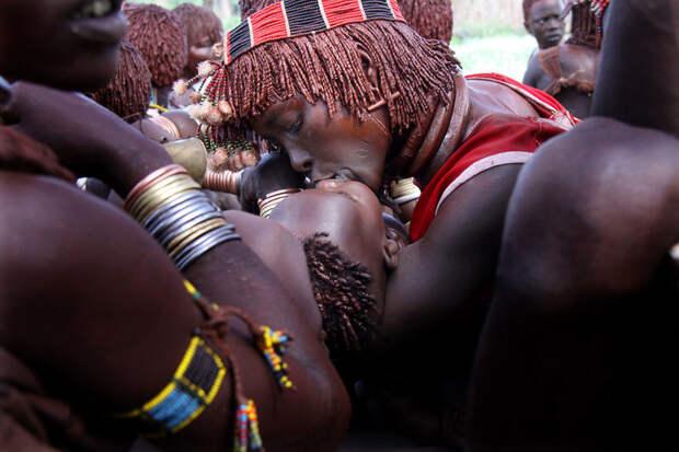 Женщина целует ребенка во время церемонии племени Хамер в долине Омо, Эфиопия вокруг света, путешествия, фотография