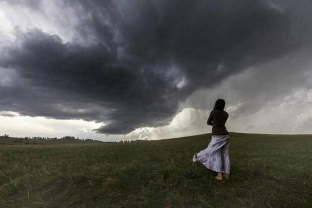 Женщину фотографируют на фоне торнадо