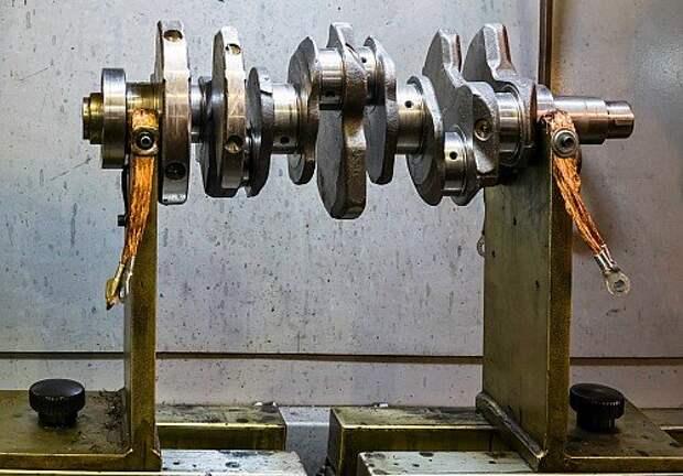Станок магнитной дефектоскопии. Коленчатый вал кладут на две опоры с обмотками (отрицательный и положительный полюсы), смазывают специальным маслом и посыпают металлическим порошком. При прохождении тока через вал созданное магнитное поле выдает скрытые трещины, характерно выстраивая над ними частицы порошка.
