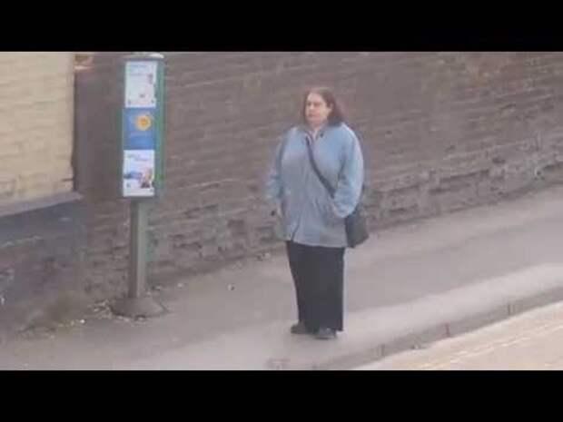 Женщина танцует на автобусной остановке