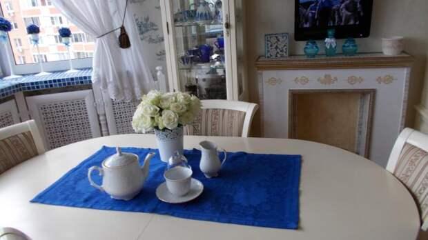 Свечной камин, белый стол с синей скатертью