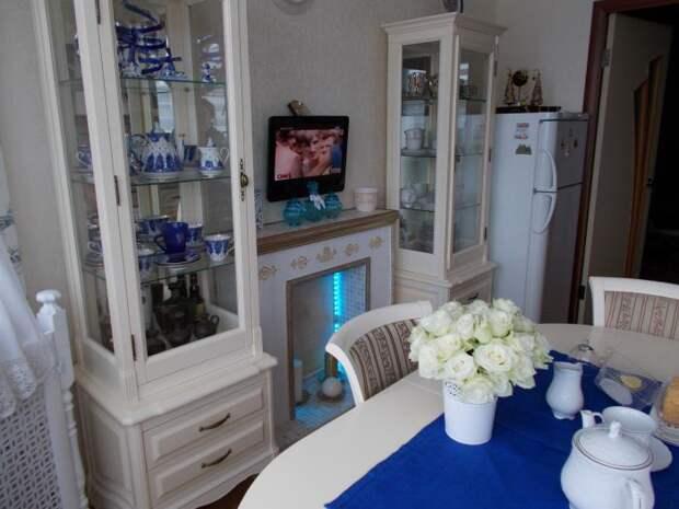 Бело-синяя кухня, витрины для посуды, камин с подсветкой