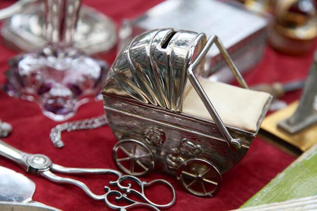 Игрушечная серебряная коляска на блошином рынке Бермондси в Лондоне