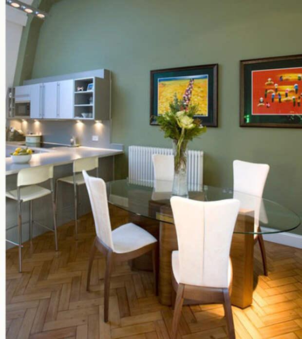 Яркие акценты в виде картин на оливковой кухне
