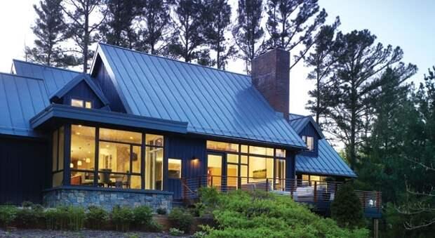 Деревянный дом с использование большого количества стекла на главном фасаде здания.
