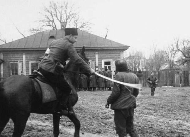 Полицай на потеху венгерским оккупантам рубит шашкой пленных советских партизан. Осень 1941 года, Украина.