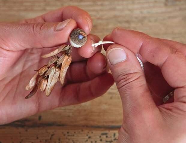 Отрежьте кусочек бисерной пряжи, концы завяжите в узелок. На тыльную сторону головы нанесите капельку клея, и узелок петельки прижмите к голове ангела.