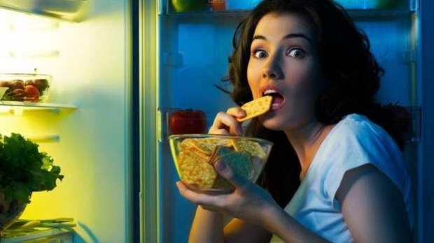 брюнетка ест печенье возле открытого холодильника