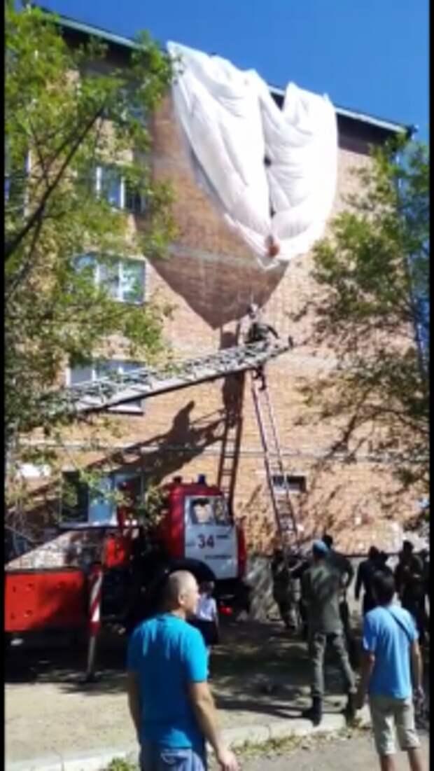 В Уссурийске парашютист зацепился за край крыши жилого дома и повис на стропах