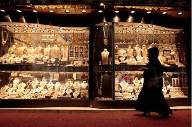 FILE PHOTO: A woman walks past gold jewellery displayed in a shop window at the Gold Souq in Dubai, United Arab Emirates March 24, 2018. REUTERS/Christopher Pike