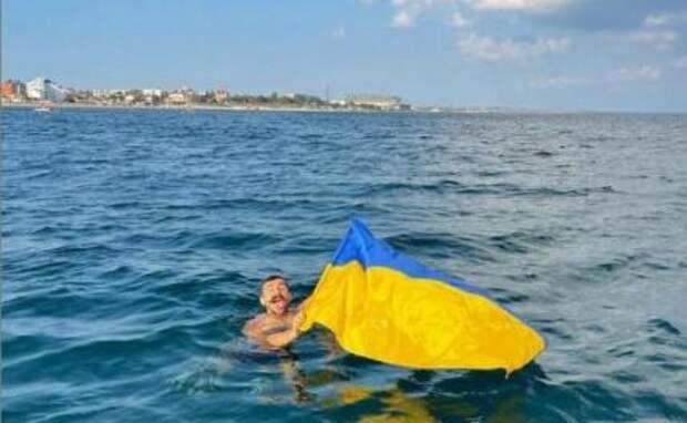 На фото: Феодосия, киевский блогер Антон Мурафа плывет с флагом Украины.