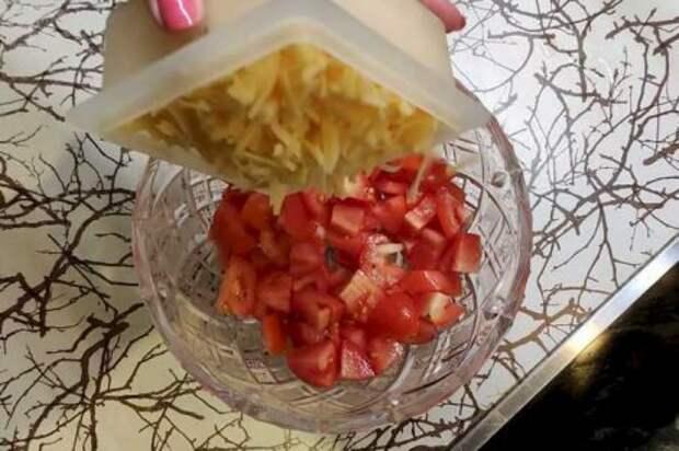 Высыпаем в салатницу нарезанные крупным кубиком  помидоры, затем сверху высыпаем натертый сыр. Затем выдавливаем чеснок.  Количество зубчиков зависит от того, насколько более нежным или более  пикантным должен получится салат. В целом - по вкусу. Зубчика 3-4 должно  хватить.