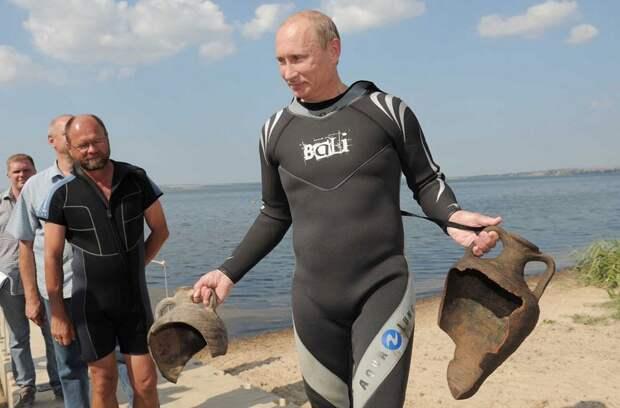 Президент РФ держит в руках две находки, сделанные им во время погружений рядом с местом археологических раскопок на полуострове Таманский, 10 августа 2011 года.
