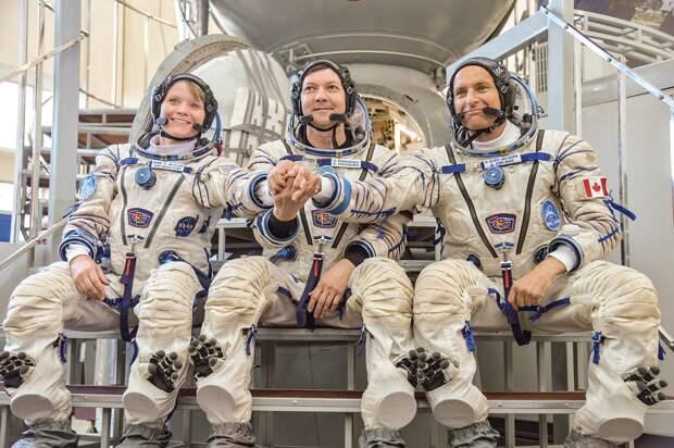 Soyuz MS-09 backup crew in front of the Soyuz spacecraft mockup.jpg
