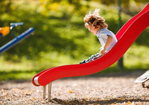 веселый маленький мальчик весело, а раздвижные на открытом воздухе. - горка на детской площадке стоковые фото и изображения