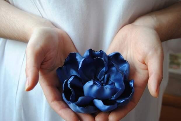 Цветок из ткани умещается в женских руках