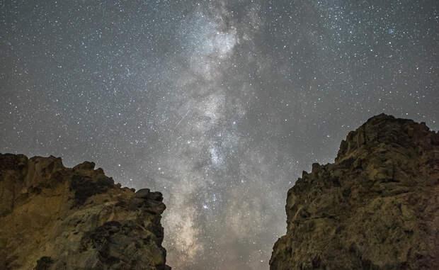 Между скал Млечный Путь простирается на ночном небе между внушительными скалами на Pfeiffer State Beach, расположенного неподалеку от Биг-Сур, Калифорния.