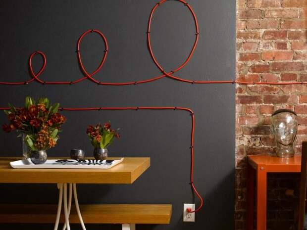 Красный провод электропитания контрастным оттенком выделяется на фоне темной стены.