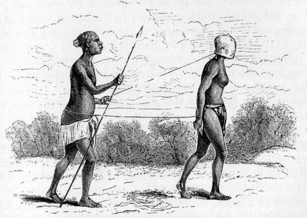 Негр-охранник конвоирует рабыню в маске (Восточная Африка, 1874 год)