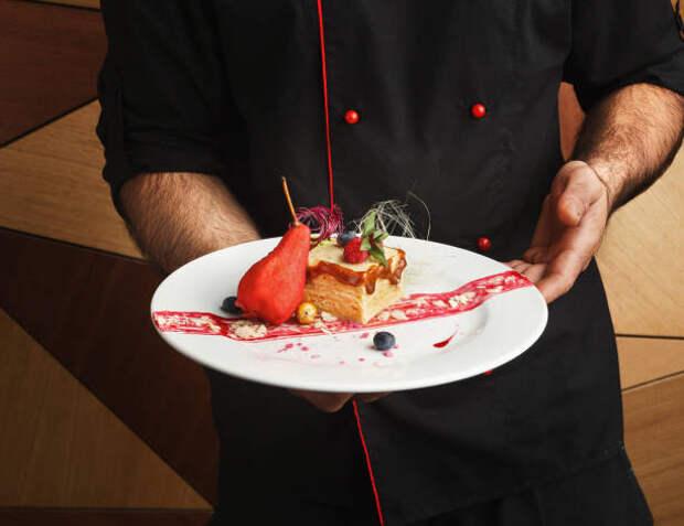 официант держит тарелку с десертом