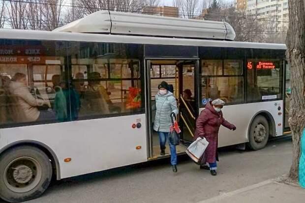 женщины выходят из автобуса в защитных масках