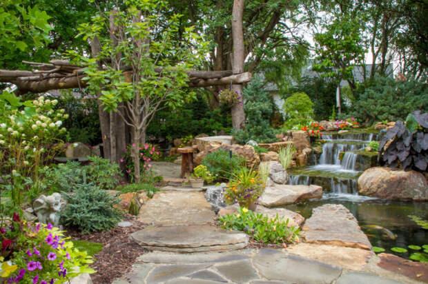 Искусственный водопад и густая растительность придадут свежести дачному участку.