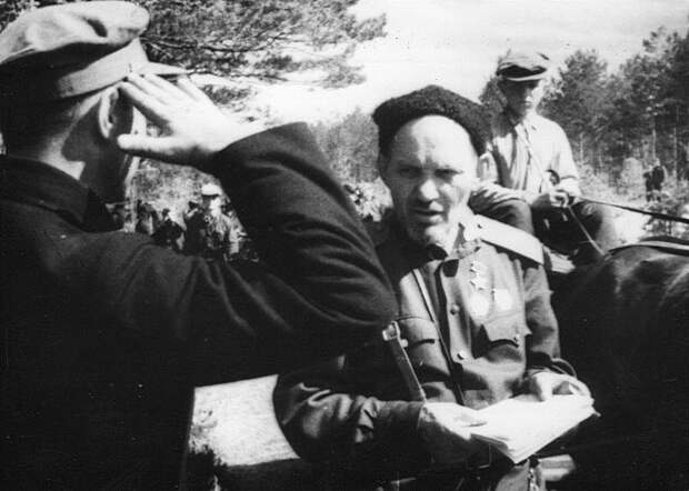 Герой Советского Союза генерал-майор С.А. Ковпак принимает рапорт партизана.