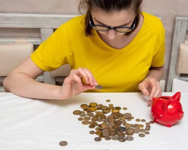 девушка в очках считает монеты из копилки