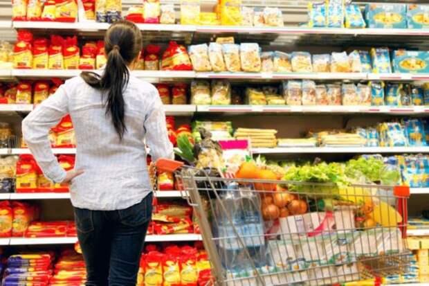 девушка с полной тележкой рассматривает продукты на полке