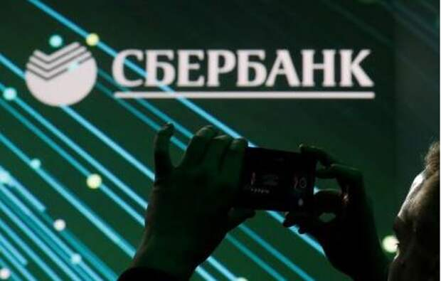 A man takes a picture of the logo of Russian bank Sberbank on a screen during a session of the St. Petersburg International Economic Forum (SPIEF), Russia June 6, 2019. REUTERS/Maxim Shemetov