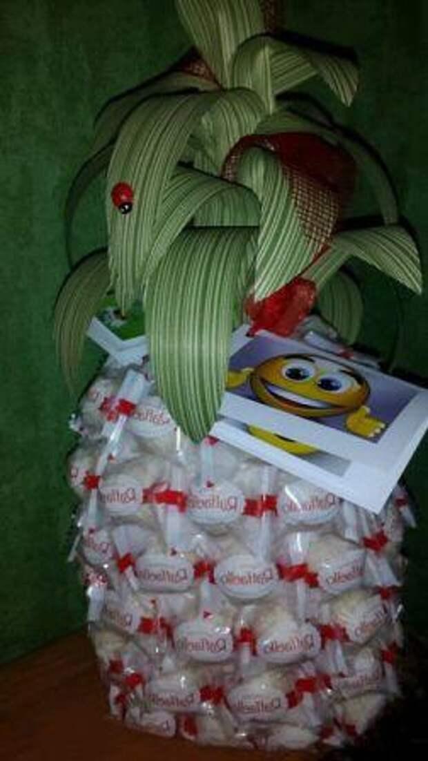 После того как вы полностью оклеили основу конфетами Рафаэлло, приступите к украшению ананаса из конфет.