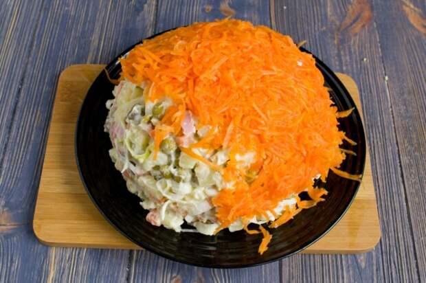 Натираем оставшуюся морковь и покрываем ею салат