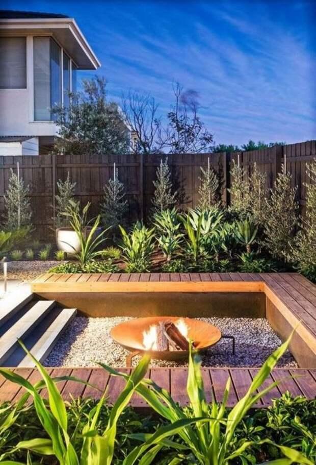 Летнее патио, углубленное в землю, с деревянными скамейками и небольшим очагом - идеальное решение для небольшого дачного участка.