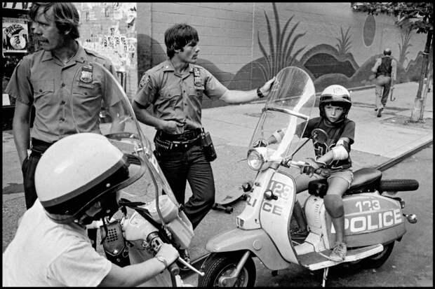 Дети мечтают стать полицейскими, они сидят на патрульном скутере.