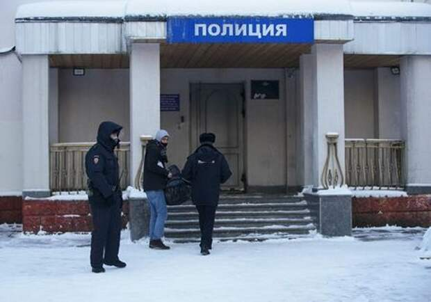 An ally of Russian opposition leader Alexei Navalny accompanied by police officers enters a police station where detained Navalny is being held, in Khimki outside Moscow, Russia January 18, 2021. REUTERS/Tatyana Makeyeva