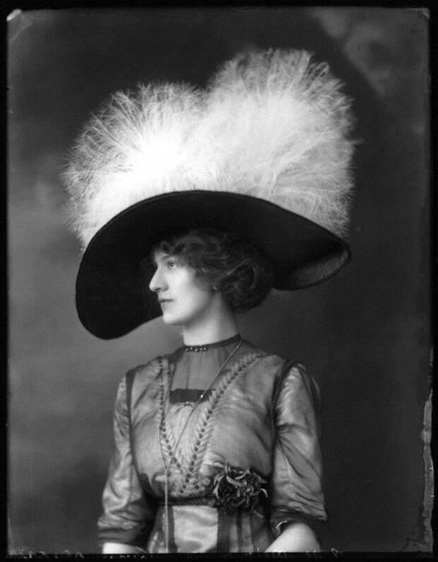 Темная шляпа, украшенная белыми перьями.