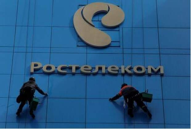 Workers wash the windows of an office building with the logo of Russia's telecoms operator Rostelecom in Moscow, Russia, May 7, 2017. Picture taken May 7, 2017. REUTERS/Sergei Karpukhin