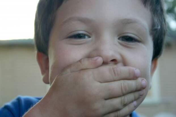 Мальчик закрыл рот ладонью