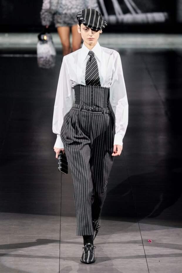 модель на подиуме в полосатом костюме с галстуком