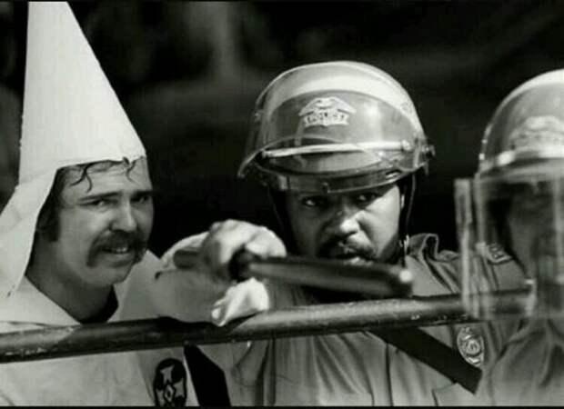 13. Темнокожий солдат защищает члена ККК от протестующих