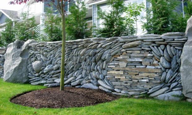 Играя с цветом, размером и кладкой камней можно создать настоящий забор-картину. /Фото: villagebookstoremn.com